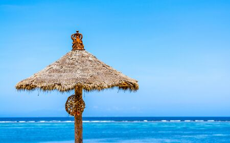 A traditionally built thatched sun shade standing on the beach on a beautiful sunny day.