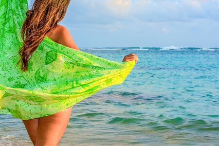 A young woman with green sarong on the beach in Bali, Indonesia