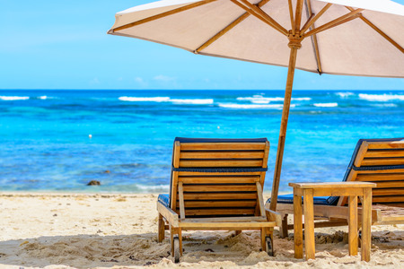lounge chair: A lounge chair at the beach under the shade of an umbrella on a beautiful beach in Bali