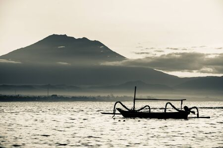 outrigger: An outrigger canoe achored with a volcano peak above the clouds in the distance.