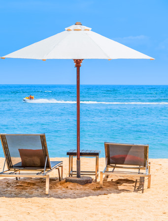 A beautiful day at the beach with sun lounger chairs under an umbrella and a Jet Ski zooming past in the distance. Stock Photo