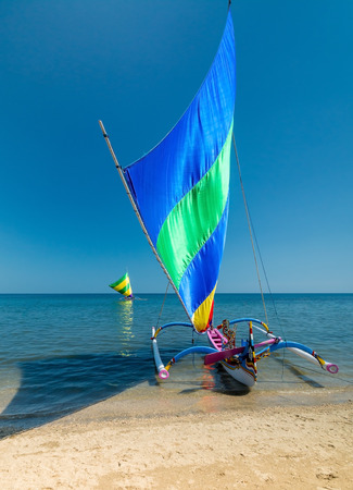 midday: A outrigger canoe from indonesia thats been converted into a sail boat for tourist hire. Perfect day for it.