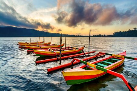 outrigger: Traditional Indonesia fishing outrigger canoes called Jakung  on the lake at sunrise tied up to a wharf.