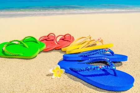 vibrance: Colored sandals on a beautiful tropical beach with the aqua colored water and seashore in the background. Stock Photo