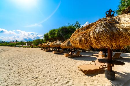 seashores: A line of beach huts under the summer sun on a tropical beach.