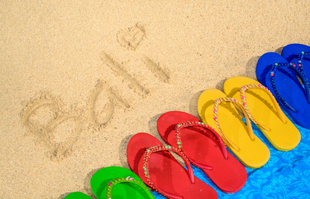 vibrance: A variety of colored sandals at the beach with Bali written in the sand.