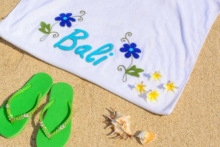 white towel: A day at the beach in Bali with a pair of green sandals. shells , frangipanis and a white beach towel.