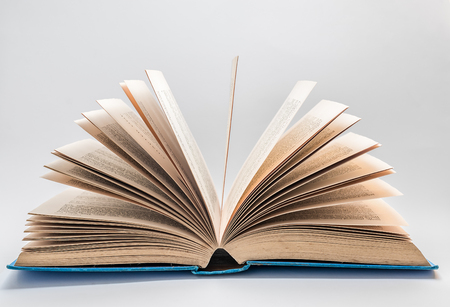 single story: An old open story book on a white background with the pages fanning out.