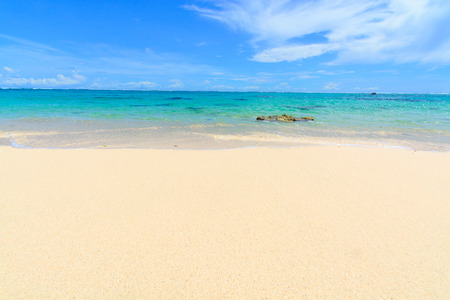 White sandy beach in Bali, with aqua coloured water and blue sky all the way to the horizon