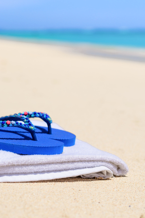 flops: A pair of blue flip flops on a white towel at the beach with the seashore blurred out in the background.