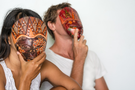 A couple hiding their faces behind masks maybe indicating that theres problems in their relationship.