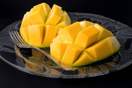 glass plate: A sliced mango on a glass plate with a fork and black background