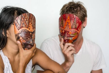 inconstant: A couple hiding their faces behind masks maybe indicating that theres problems in their relationship.