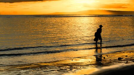 he is a traditional: A silouette of a traditional fisherman at sunrise as he wanders along the beach looking to throw his net. Stock Photo