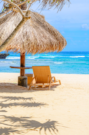 perfect waves: A thatched roof beach hut with lounge chair on the sand. Stock Photo