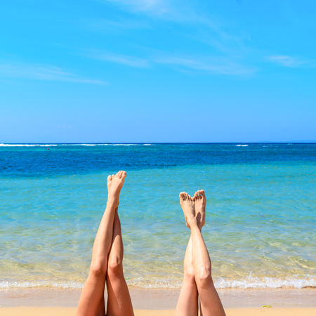Womens legs up with tropical  beach background on a beautiful summers day. Stock Photo