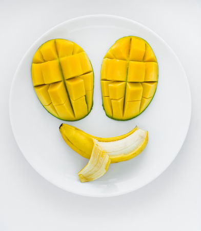 poking: A face made from mangoes for eyes and a banana for mouth with a tongue poking out.