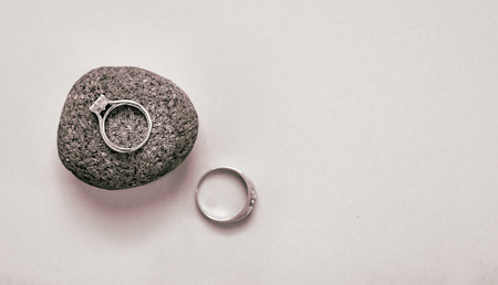 whitespace: His & hers wedding rings on a white background with her ring in sharp focus and sitting on a textured stone.