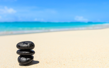Three black stones stacked up on a white tropical sandy beach with blue sky and the ocean in the background Stock Photo