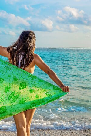 sarong: A young woman with green sarong on the beach in Bali, Indonesia