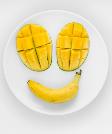 smily: A smily face made from tropical fruit, two  mangoes and a banana on a white plate with white background. Stock Photo