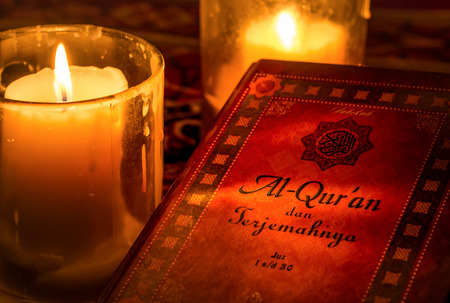 reading material: The cover of holy Koran with candle light. Stock Photo