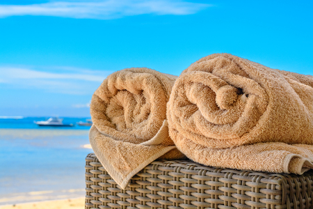 A beauiful day at the beach with two towels rolled up on a cane side table and the sandy beach front in the background.