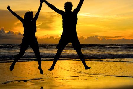 백그라운드에서 아름 다운 오렌지 일몰과 함께 해변에서 손을 잡고 점프 젊은 부부.