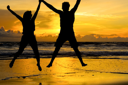 aplomb: A young couple jumping while holding hands at the beach with a beautiful orange sunset in the background.