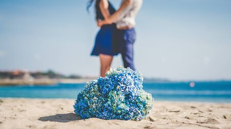 A couple honeymooning at the the beach with a flower bouquet in the foreground.