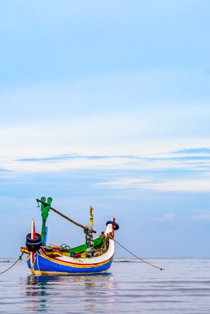 A Traditional Indonesian fishing boat (Jukung) anchored just off the beach early in the  morning on a cloudy day. Stock Photo