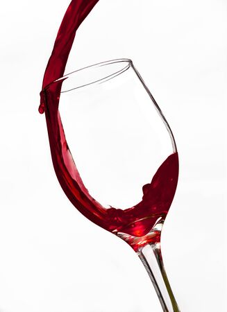 Red wine being popured quickly into a glass with white background.