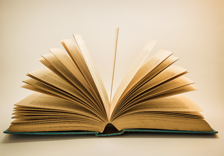 book pages: An old open story book on a white background with the pages fanning out.