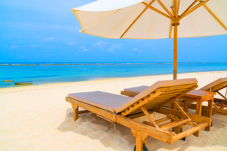 daybed: Daybed and umbrella on a tropical white sandy beach in Bali.