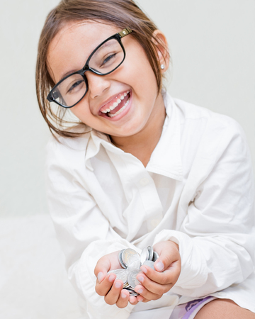 Young Asian girl with glasses holding handfull of coins laughing. 免版税图像