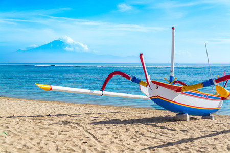 outrigger: A traditional Indonesian outrigger canoe still used for day to day fishing by locals sits on the beach on a beautiful blue sky day.