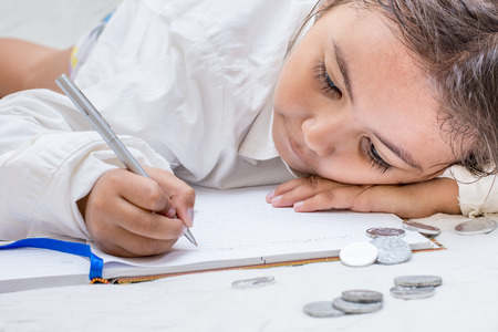 Young Asian girl writing counting coins and writing in book.