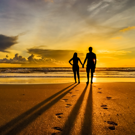 A silhouetted couple walking and watching the sunset on a tropical beach in Bali.