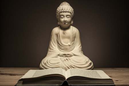 Buddha statue with book in moody light scene.