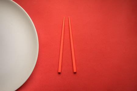 Chopsticks on red background with white plate. Reklamní fotografie