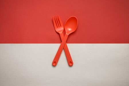 Red fork and spoon crossed over Indonesian flag Banque d'images