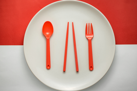 White plate with red forkspoon & chopsticks over Indonesian flag, concept image. Stock Photo