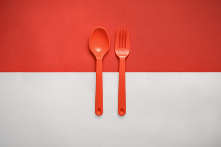 conceptual image of Indonesian flag with plastic fork and spoon.