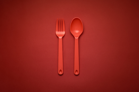 Red Fork & Spoon on red background under spotlight monochromatic color scheme. Archivio Fotografico - 96182177