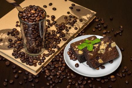 Coffee beans in glass with chocolate macadamia nut brownie - dark and moody coffee shop scene.