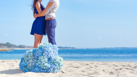 Man and woman together at the beach with blue flowers in-focus in the foreground and copy space.
