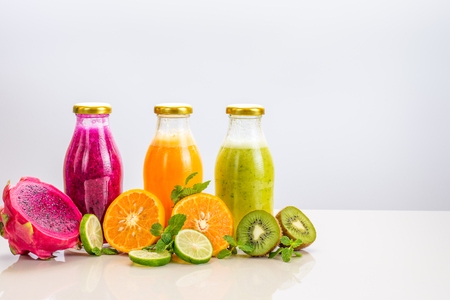 Three flavours of fruit juice in bottles with a straw islolated on white background with copy space. Stock Photo