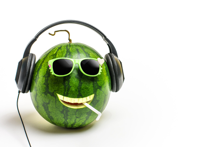 Happy watermelon face with headphones on listening to music with copy space for text. Stock Photo