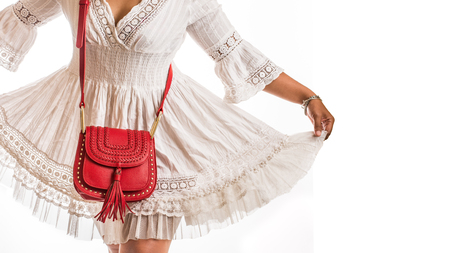Woman wearing white dress with leather red hand bag and copy space.