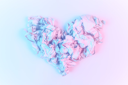 Pastel pink and blue abstract background image made from crumpled paper arranged into a heart shape. Stockfoto